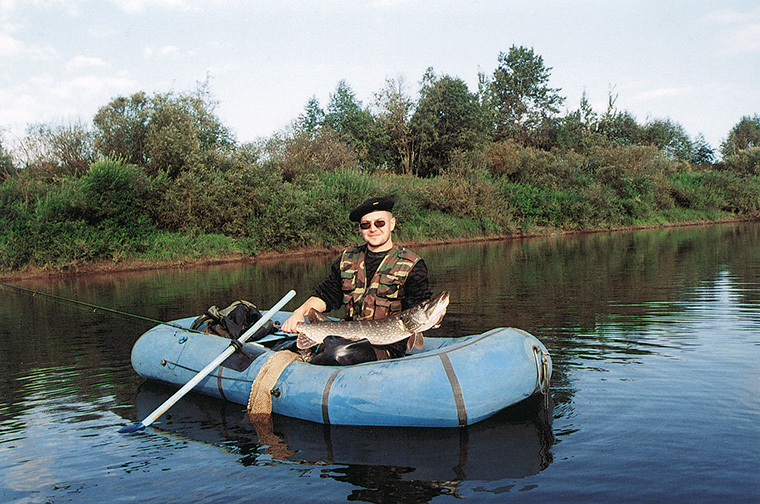 рыболов со щукой в лодке