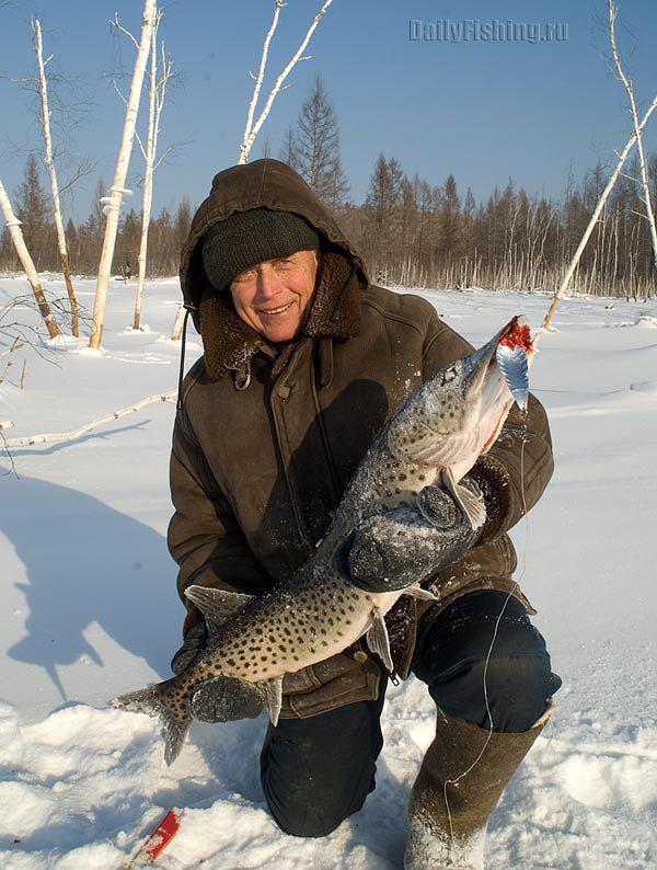 рыболов со щукой на льду буреи